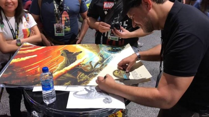 Animator Glen McIntosh signing a poster for one of the Jurassic Park films he has worked on.